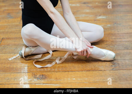 Cropped image of a ballerina in pointes having pain in ankle - Stock Photo