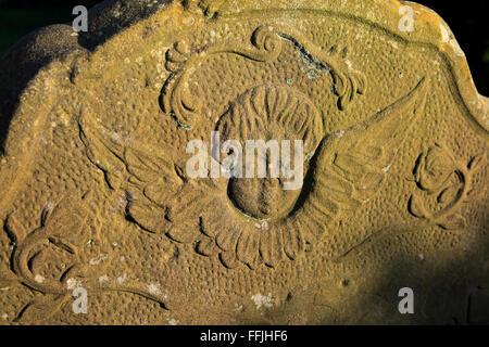 Weathered carved image on stone gravestone of cherub angel with wings, Rasmsholt, Suffolk, England, UK - Stock Photo