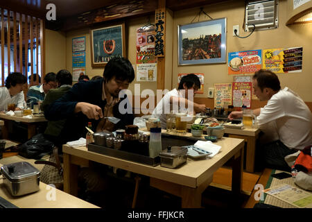 Asian people eating in Tokyo, Japan, Asia. Woman dining in traditional Japanese restaurant, cooking food. Clients, - Stock Photo
