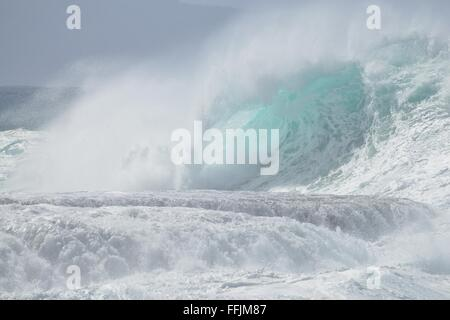 A beautiful large whitewater wave crashing on the beach. The image was captured in Oahu Hawaii during the surfing - Stock Photo