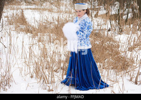 Russian young woman in traditional russian clothes in winter meadow - Stock Photo