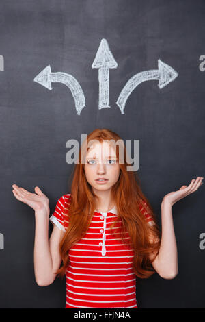 Sad confused young woman choosing direction over blackboard background - Stock Photo
