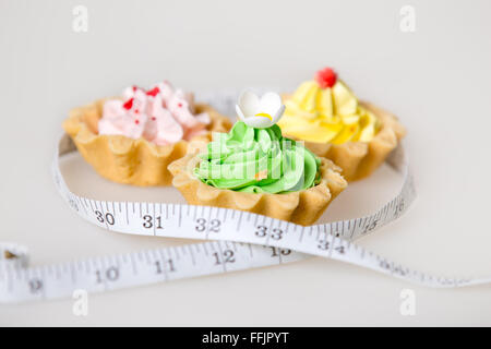 Three colorful green, pink and yellow tart cakes wrapped in measuring tape on white background, unhealthy lifestyle - Stock Photo