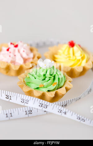 Three colorful tart cakes wrapped in measuring tape on white background, weight loss concept, studio - Stock Photo