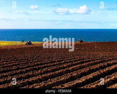 Ploughing Ballintoy County Antrim Northern Ireland Causeway Coast Farming Tractors Fields - Stock Photo