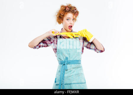 Attractive playful young housewife with red curly hair posing with yellow protective gloves over white background - Stock Photo