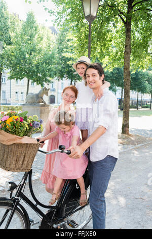Family with two children pushing bicycle in city - Stock Photo