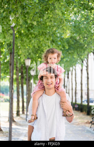 Father carrying daughter on his shoulders - Stock Photo