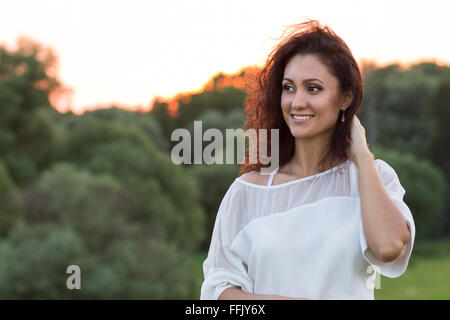 Young happy woman with black frizzy hair standing outdoors against woods in the evening. Portrait of hispanic smiling - Stock Photo