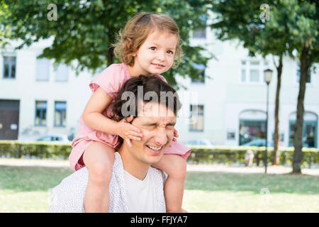Father carrying daughter on shoulders - Stock Photo