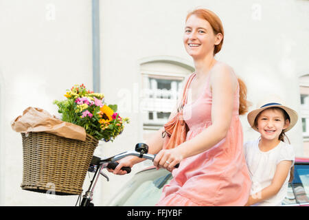 Mother and daughter cycling in city - Stock Photo