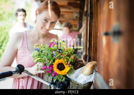 Portrait of mid adult woman with flowers - Stock Photo