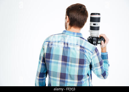 Back view portrait of a male photographer holding photo camera isolated on a white background - Stock Photo