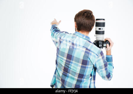 Back view portrait of a male photographer holding photo camera and pointing on something isolated on a white background - Stock Photo
