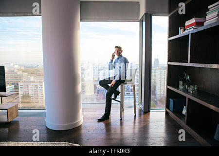 Businessman in apartment on the phone - Stock Photo