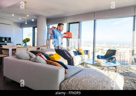 Man in apartment relaxing arms outstretched - Stock Photo