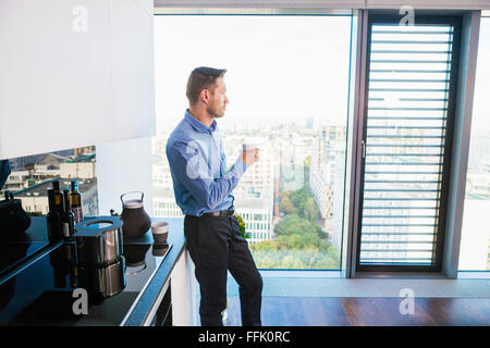 Businessman in apartment having a coffee break - Stock Photo