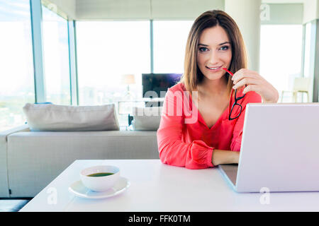 Woman in apartment using tablet computer - Stock Photo
