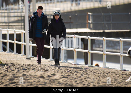Aberystwyth, Wales, UK. 15th February 2016.  UK weather: Two people out enjoying a day of  warm winter sunshine - Stock Photo