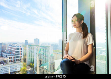 Woman in apartment looking through window - Stock Photo