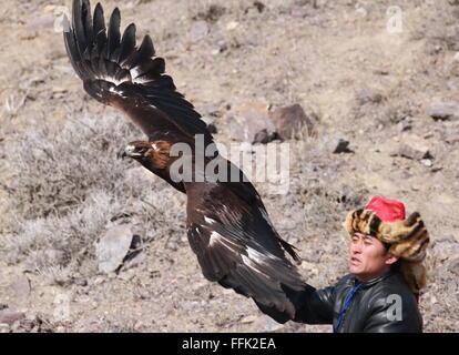 Almaty Region, Kazakhstan. 15th Feb, 2016. A berkutchi (Kazakh eagle hunter) with a golden eagle at Sonar 2016, - Stock Photo