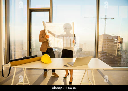 Two architects in office examining blueprint - Stock Photo