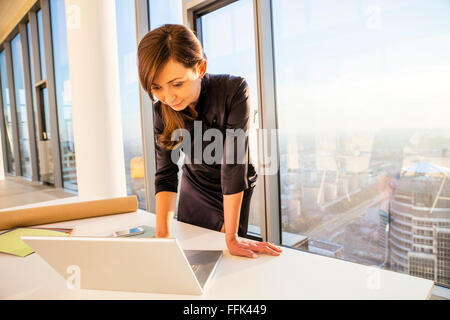 Female architect in office working on laptop - Stock Photo