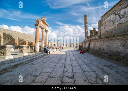 Pompeii forum, a group of tourists pose for a photo in the forum in the ancient ruined city of Pompeii, Italy. - Stock Photo