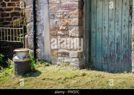 Milk churn outside barn door, Carlton, Yorkshire Dales, England - Stock Photo