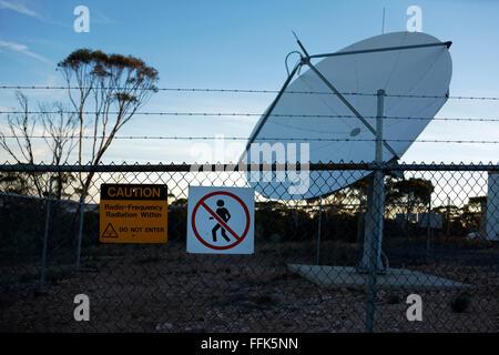 Radiation Warning Sign on fence with Satellite Dish, Norseman, Western Australia - Stock Photo