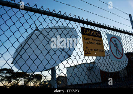 Radiation Warning Sign on fence with Satellite Dish, Norseman,  Western Australia - Stock Photo