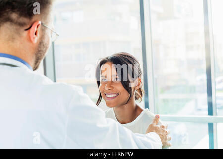 Doctor tapping coworker on the shoulder - Stock Photo