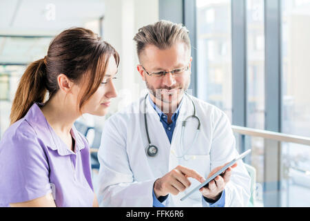Doctor and nurse looking at digital tablet in hospital - Stock Photo