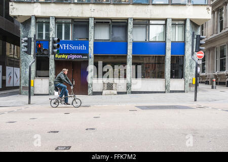 Cyclist passes the ancient London Stone, an historic 900 year old stone hidden behind an iron grille on Cannon Street, - Stock Photo