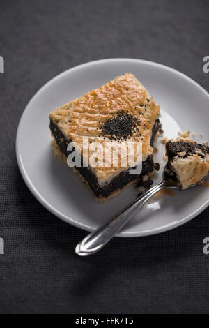 One individual poppy seeds tartlet on a white plate, one bite taken out, with a spoon, on a grey background. - Stock Photo
