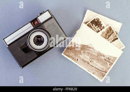 Vintage photo camera and old photos on a gray table - Stock Photo