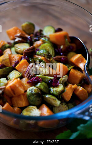 Roasted Brussels sprouts, sweet potatoes, pecans and cranberries  in a bowl on a rustic wooden table - Stock Photo
