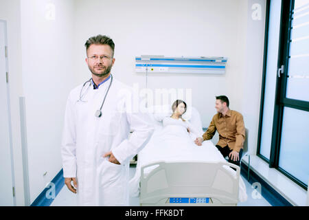 Doctor with patient in sick room of hospital - Stock Photo
