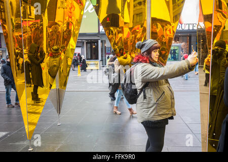 Visitors do selfies with their reflections in 'Heart of Hearts', the winner of the Times Square Valentine Heart Design in Times Square in New York on Tuesday, February 9, 2016. The sculpture by Collective-LOK creates a golden kaleidoscopic space that mirrors the cacophony and visual stimulation that attracts so many visitors to Times Square. The sculpture will be on view until March 6. (© Richard B. Levine)
