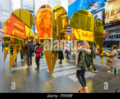 Visitors view their reflections in 'Heart of Hearts', the winner of the Times Square Valentine Heart Design in Times Square in New York on Tuesday, February 9, 2016. The sculpture by Collective-LOK creates a golden kaleidoscopic space that mirrors the cacophony and visual stimulation that attracts so many visitors to Times Square. The sculpture will be on view until March 6. (© Richard B. Levine)