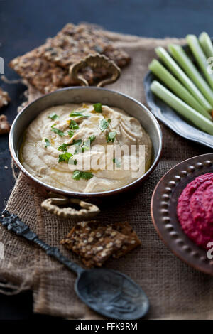 Hummus and beetroot hummus with crisp bread, carrots and celery - Stock Photo