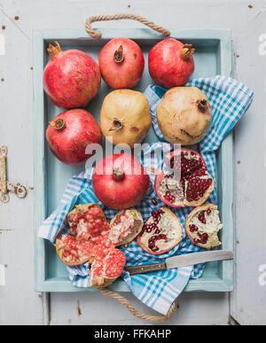 Red and white pomegranates and knife on kitchen towel in blue tray over light painted wooden backdrop, top view - Stock Photo