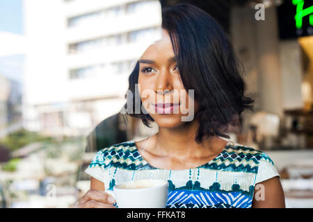 Mixed race woman takes a coffee break - Stock Photo