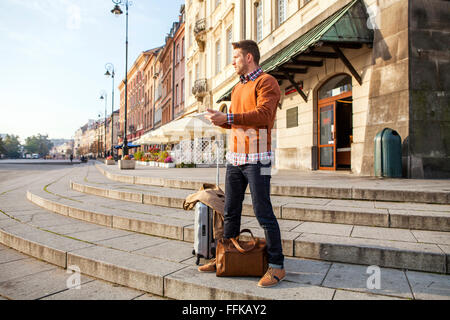 Man on a city break using digital tablet - Stock Photo