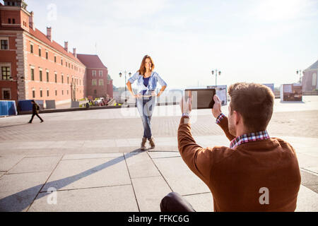 Mid adult man taking a picture of girlfriend - Stock Photo