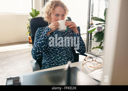Portrait of young woman sitting at her desk drinking coffee and looking at computer monitor. Thoughtful designer - Stock Photo