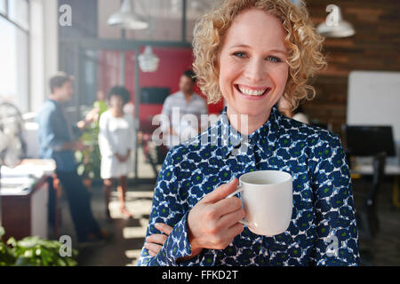 Portrait of cheerful female designer holding a cup of coffee. She is standing in office with colleagues discussing - Stock Photo