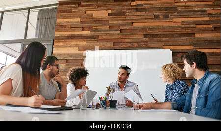 Group of business people having meeting in a board room in an office. Creative team sitting at the table discussing - Stock Photo