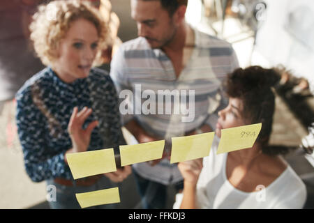 Three business people having a meeting in office. They are standing in front of glass wall with post it notes and - Stock Photo