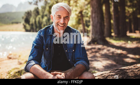 Portrait of happy mature man sitting near a lake looking at camera and smiling. Senior caucasian man sitting on - Stock Photo